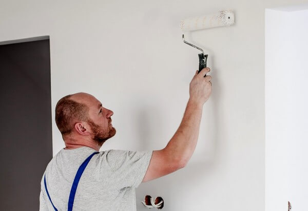 Pintor pintando pared