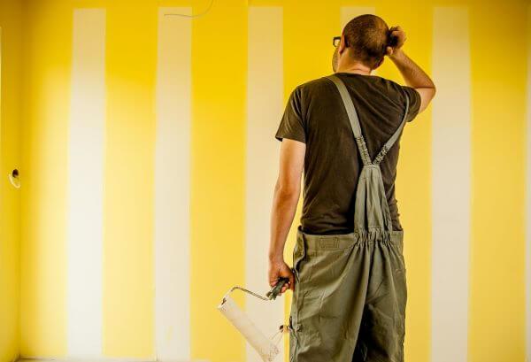 Pintor pintando rayas en la pared